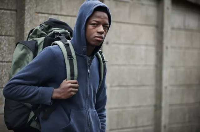 Young black man in hoodie with backpack