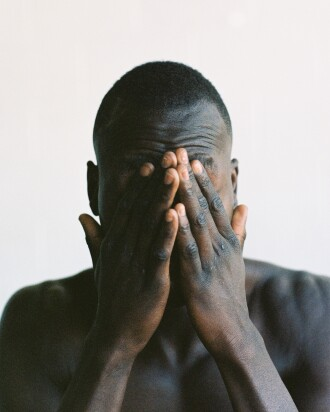 Black man covering his face with his hands